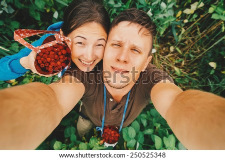 Happy young couple in love taking self-portrait in summer garden with raspberries. Top view - stock photo