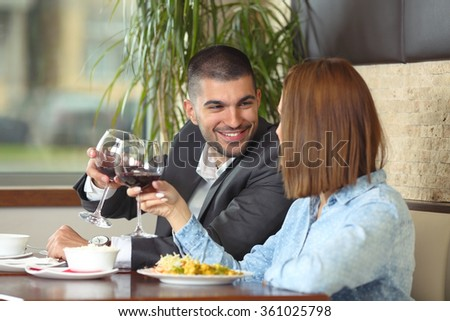Happy young couple in love toasting while having a lunch at the restaurant - stock photo