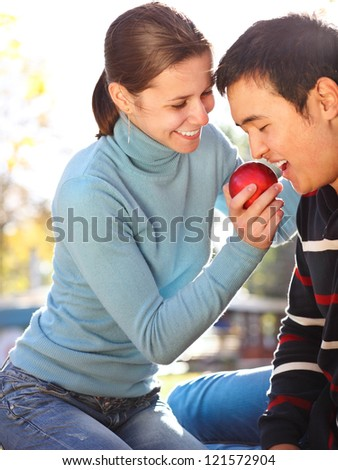 Happy young couple in love with apple outdoors - stock photo