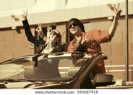 Happy young couple in new convertible car - stock photo