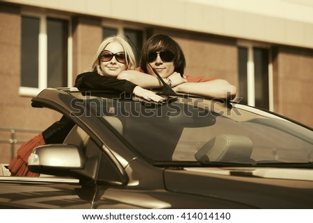 Happy young couple in new convertible car
