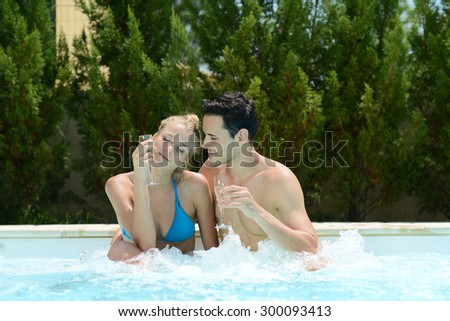happy young couple in spa resort drinking champagne in whirlpool bath