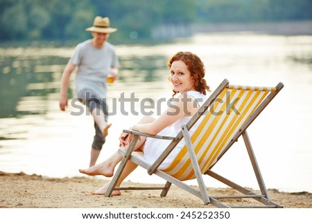 Happy young couple in summer on beach of a lake - stock photo