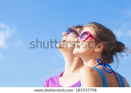 happy young couple in sunglasses smiling looking at the sky