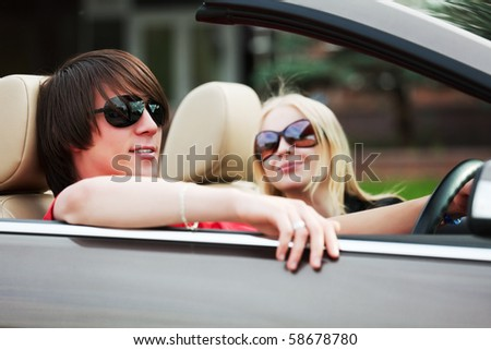 Happy young couple in the convertible car.