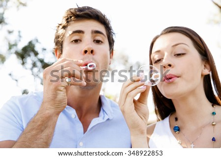 Happy young couple in the park blowing bubbles