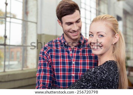 Happy young couple in their apartment standing close together in front of a window with the pretty blond wife giving the camera a beaming smile - stock photo