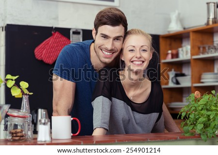 Happy young couple in their kitchen posing with their heads close together behind the counter smiling at the camera - stock photo