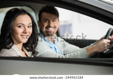 Happy young couple in their new car are looking at the camera. - stock photo
