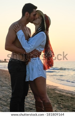 Happy young couple in their twenties, in wet cloths, embracing and kissing at the beach just before sunset. - stock photo