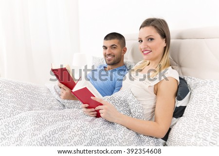 Happy young couple is reading books in bed. Focus on beautiful smiling young woman lying in bed with her boyfriend and looking at camera. - stock photo