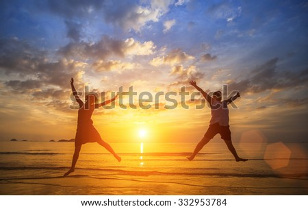 Happy young couple jumping in Sea beach during a beautiful sunset. - stock photo