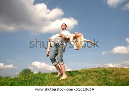 Happy young couple  jumping in sky above a green meadow - stock photo