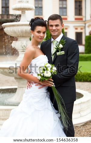 Happy young couple just married posing for photographer - stock photo