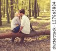 happy young couple kissing and hugging, sitting on a tree - stock photo