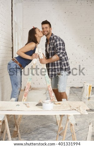 Happy young couple kissing on ladder at home renewal. - stock photo