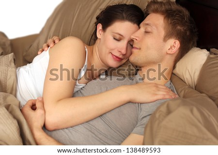 Happy young couple laying in bed