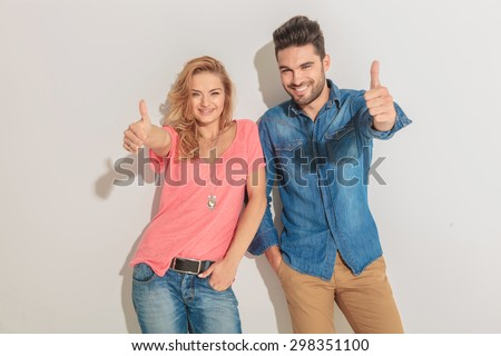Happy young couple leaning on a wall while showing the thumbs up gesture. - stock photo