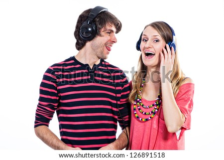 Happy young couple listening to a music isolated on a white background