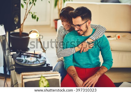 Happy young couple listening to music indoor, cuddle each other