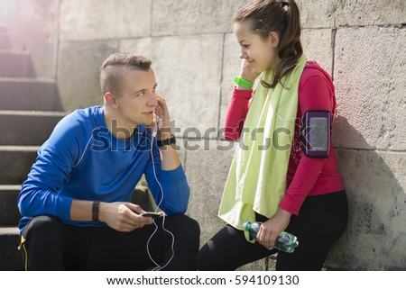 Happy young couple listening to music on the earphones smiling and laughing after jogging on a sunny day