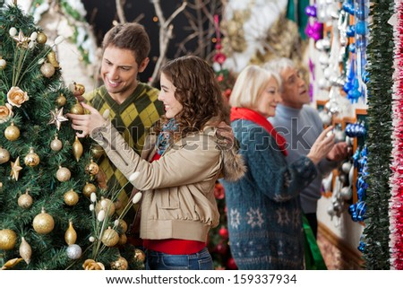 Happy young couple looking at Christmas tree with parents shopping in background at store - stock photo