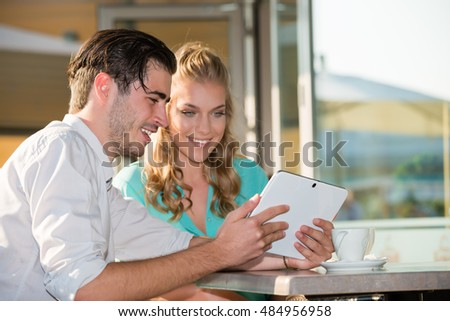 Happy young couple looking at digital tablet in outdoor cafe