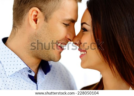 Happy young couple looking at each other over white background