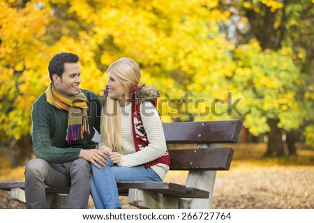 Happy young couple looking at each other while sitting on park bench during autumn - stock photo