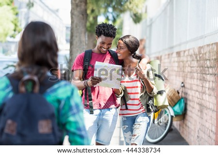 Happy young couple looking at map and talking - stock photo