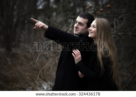 Happy young couple looking at something and pointing