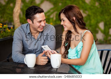 Happy young couple looking at something on a cell phone while having coffee at a restaurant