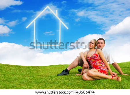 Happy young couple looking at the sky dreaming about their future house - stock photo