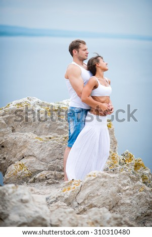 Happy Young Couple lovers man and woman walking in the mountains - stock photo