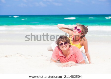 happy young couple lying and having fun at tropical beach - stock photo