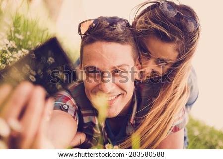 Happy young couple lying at the grass and taking selfie with smart phone