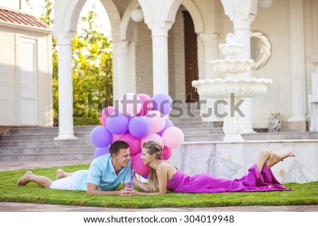 Happy young couple lying down on the lawn in front of their villa and holding colorful balloons - stock photo