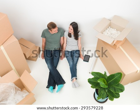 happy young couple lying on floor with boxes around them. moving house - stock photo