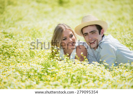 Happy, young couple lying on front in chamomile field, copy space - stock photo