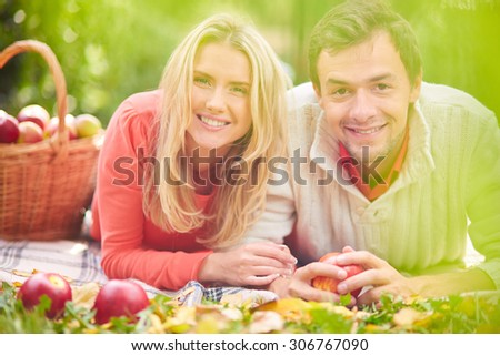 Happy young couple lying on grass in park - stock photo