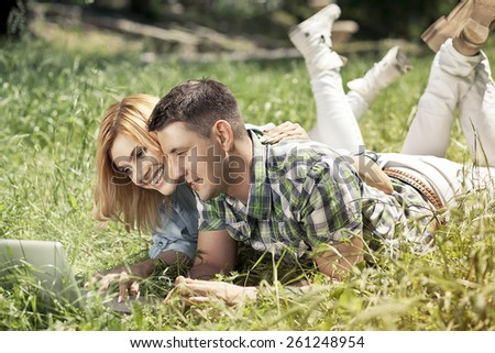 Happy young couple lying on the grass, looking at laptop and smiling. Relationship  and learning concept. - stock photo