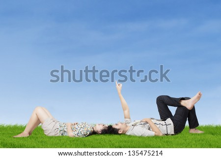 Happy young couple lying on the grass while pointing to copy space in the sky - stock photo