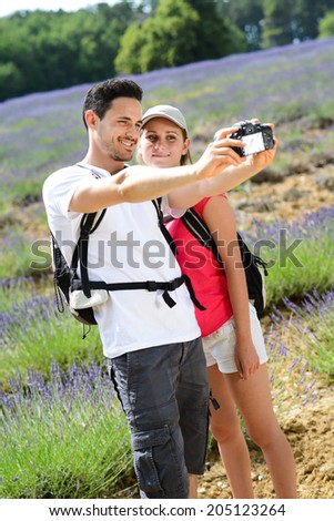 happy young couple making a selfie with camera in countryside during summer trekking - stock photo