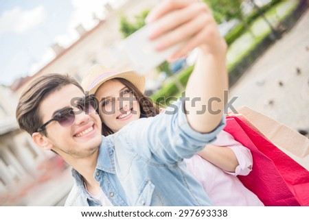 Happy young couple making selfie on phone, woman holding shopping bags. - stock photo