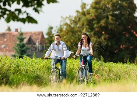 Happy young couple - man and woman - cycling in summer in nature - stock photo