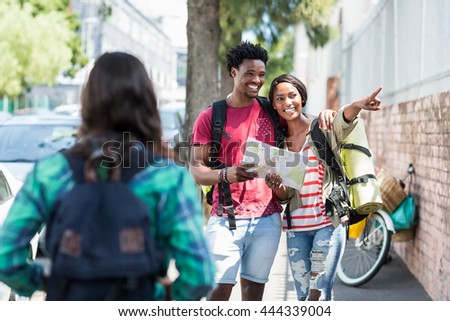 Happy young couple map and pointing outdoors - stock photo