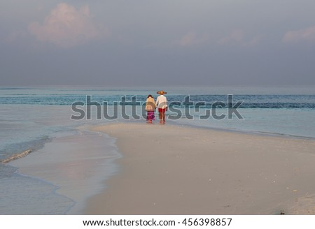 Happy young couple meets sunset on a tropical beach. Lovers in full body length on beach. Back rear view