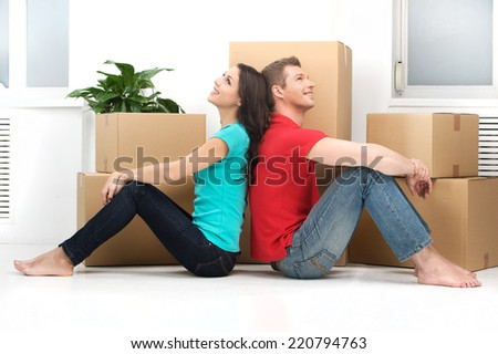 happy young couple moving in new home. man and woman sitting on floor back to back