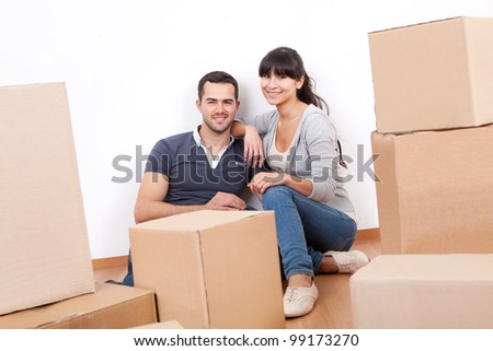 Happy young couple moving into new house - stock photo