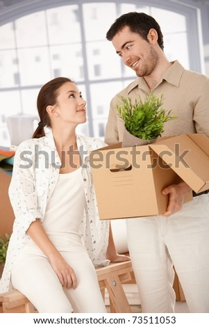 Happy young couple moving to new house, unpacking boxes, smiling at each other.? - stock photo